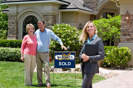 Photo of a Home with Sold Sign with owners and Real Estate Agent
